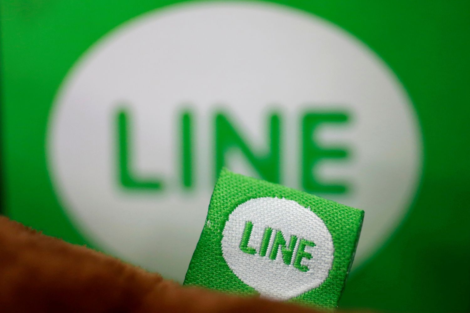 The logo of free messaging app Line is pictured on a smartphone and the company's stuffed toy in this photo illustration taken in Tokyo in 2014. (Reuters photo)