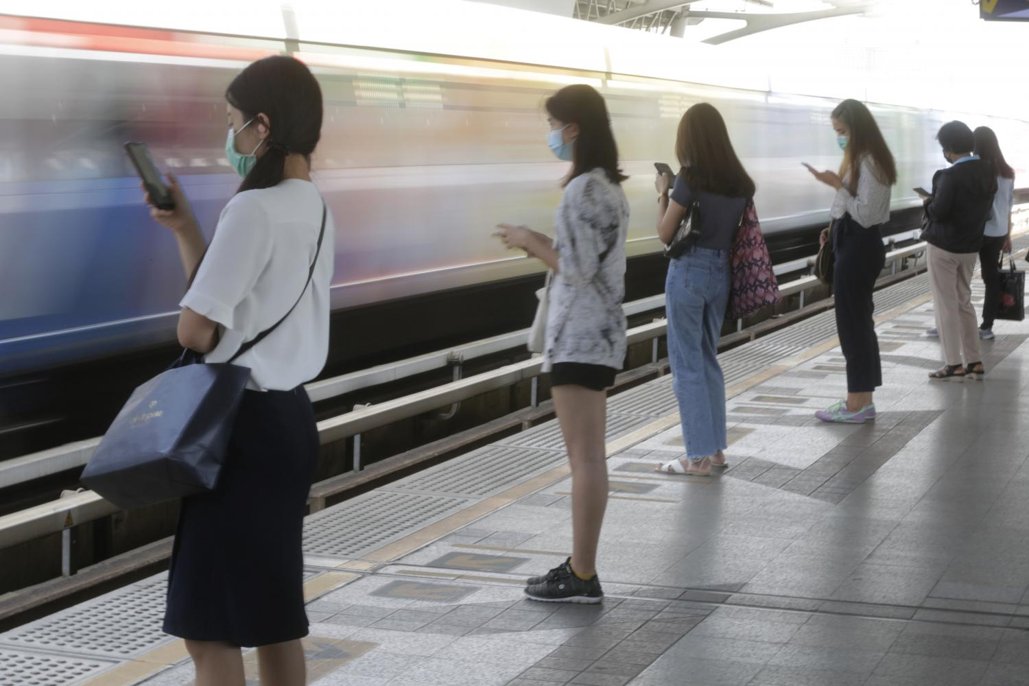 People are glued to their phones while waiting for the skytrain at Victory Monument station in Bangkok. (Photo by Pornprom Satrabhaya)