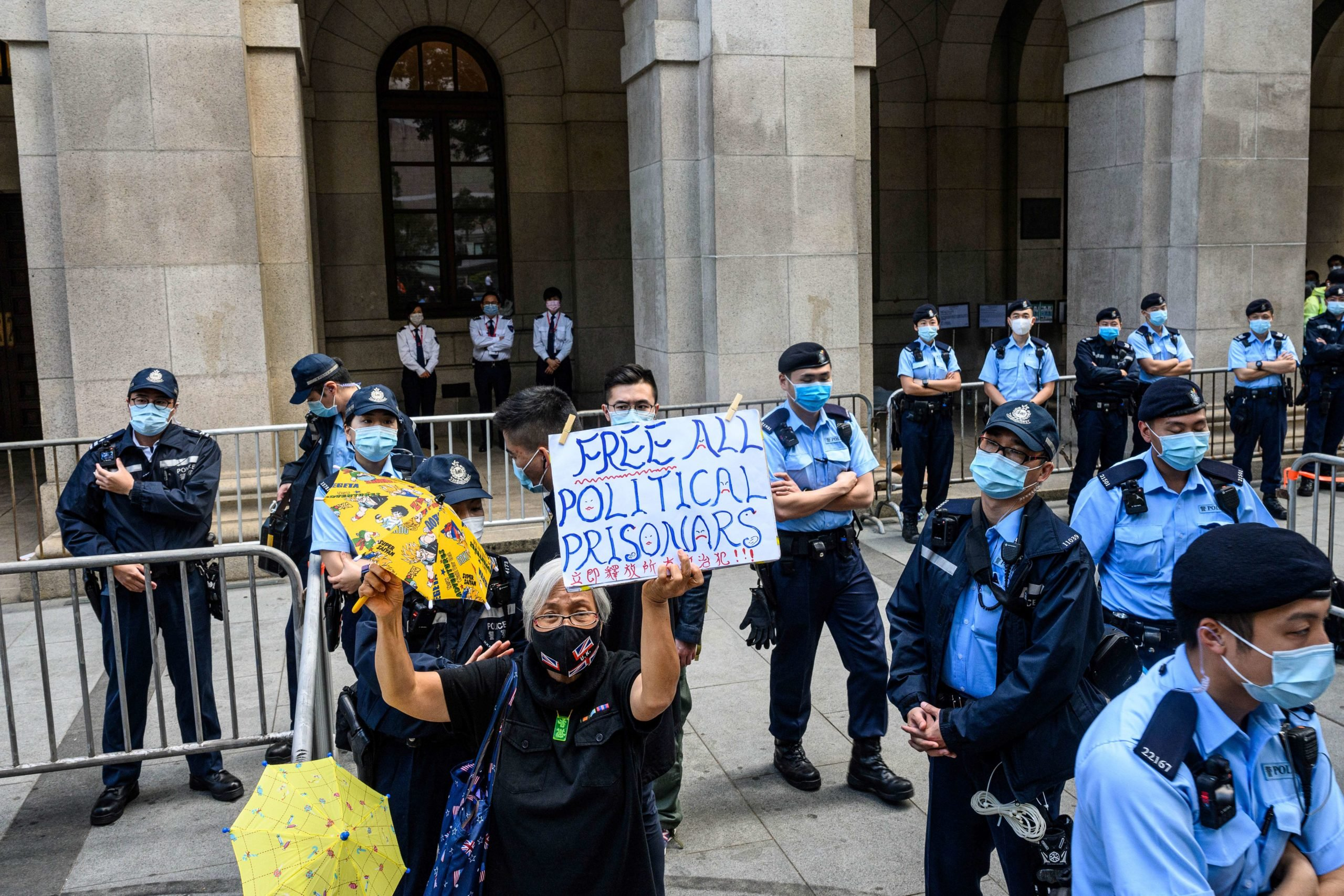 A pro-democracy activist holds up a placard as police stand guard outside the Court of Final Appeal in Hong Kong on February 1, 2021. (ANTHONY WALLACE/AFP via Getty Images)